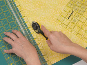 """Walk"" your fingertips, rolling the rotary cutter parallel to your fingers."