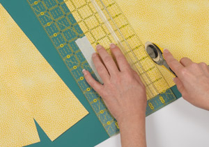 "Use a piece of masking tape on the ruler as a reminder of the fabric strip width you're cutting—this strip measures 3-1/2""."